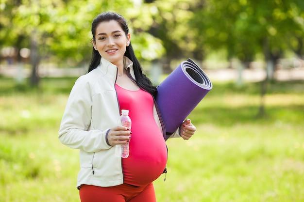 Молодая беременная женщина делает упражнения йоги.