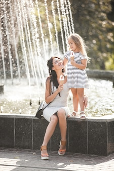 彼女の母親と一緒にアイスクリームを食べるかわいい女の子