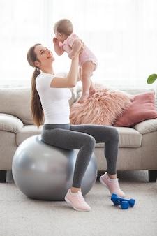 Молодая красивая мама работает со своим маленьким ребенком дома