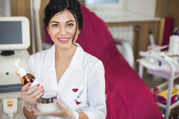 Молодая привлекательная женщина косметолог в ее салоне, сидя и улыбка на камеру.