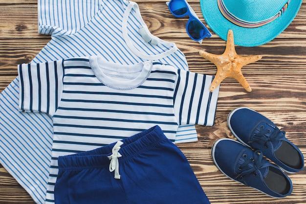 子供服のフラットはまだ。子供のワードローブ。小さな男の子のためのビーチと休暇の服。木製の背景