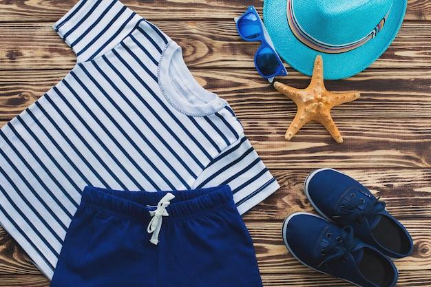 Плоская еще детская одежда. детский гардероб. пляж и одежда для отдыха для маленького мальчика. деревянный фон