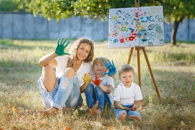 幸せな家族が屋外に描画します。若い母親が彼女の小さな子供たちと楽しんで