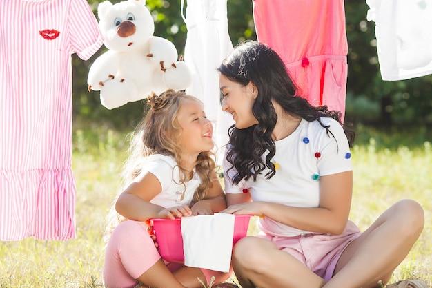 Милая маленькая девочка и ее мать, прачечная