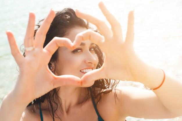 カメラに彼女の手で心を作るビーチで若いきれいな女の子。夏には美しい少女