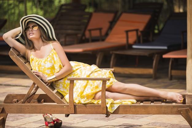 ラウンジャーで屋外でリラックスした女性。帽子の女性。夏の若い女性。黄色のドレスを着ている女性。