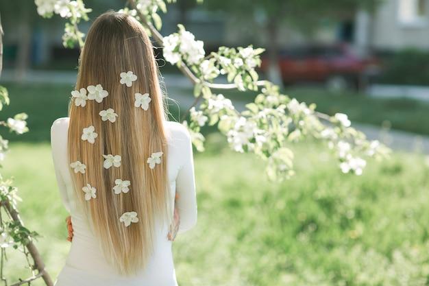 彼女の髪に花を持つ長いブロンドの髪とカメラの後ろ側に立っている認識できない女性。春の背景の女性。屋外の女性。