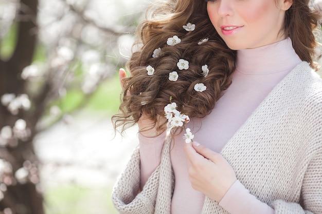Женщина с вьющимися волосами на открытом воздухе на фоне весны. непознаваемая дама со светлыми и длинными здоровыми волосами. девушка стрижка крупным планом еще
