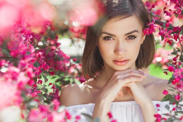 完璧な滑らかな肌を持つ若い美しい女性の肖像画を閉じます。花の魅力的な女性。美しい女性の顔の肖像画。
