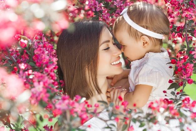 彼女の小さな女の赤ちゃんを持つ若い美しい母親の肖像画。愛する家族の静止画をクローズアップしてください。ピンクの花で彼女の子供を押しながら笑顔の魅力的な女性。