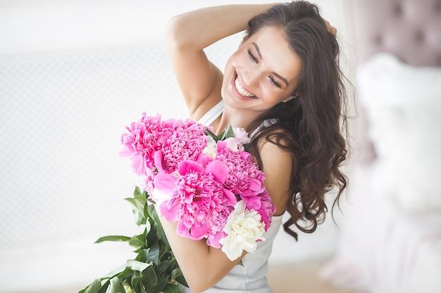 花を持つ若い魅力的な女性