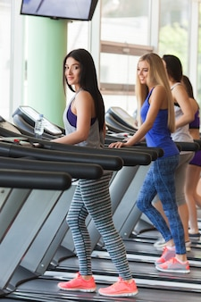 トレッドミルで実行されている良い形の美しい女の子のグループ。きれいな女性がジムでトレーニングします。女の子はカメラに微笑んでいます