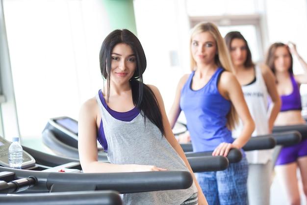 Группа красивых девушек в хорошей форме бегает по беговым дорожкам. красивые женщины, тренировки в тренажерном зале. девушка улыбается на камеру