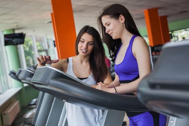 Две красивые женщины пытаются включить беговую дорожку в тренажерном зале в помещении. красивые девушки тренируются в тренажерном зале. группа начинающих по фитнесу пытается тренироваться