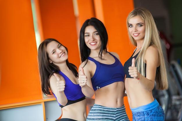 Три привлекательные девушки с стройными телами в спортивной одежде в тренажерном зале, улыбаясь в камеру и показывая большой палец вверх