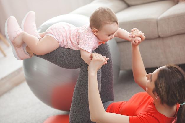 若い可愛い母親が自宅で彼女の小さな子供と一緒にワークアウト