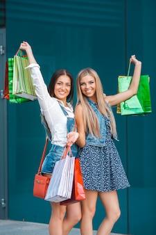 屋外の買い物袋を持つ若い魅力的女性