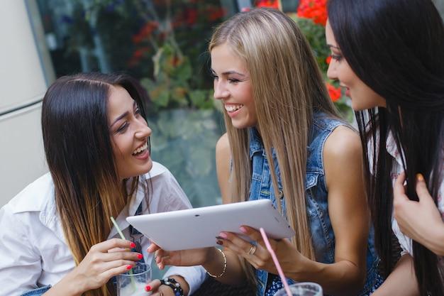 オンラインショッピングを行う陽気なガールフレンド。カフェテリアで若い笑う女性。楽しんで笑顔の若い女の子。友達のグループ