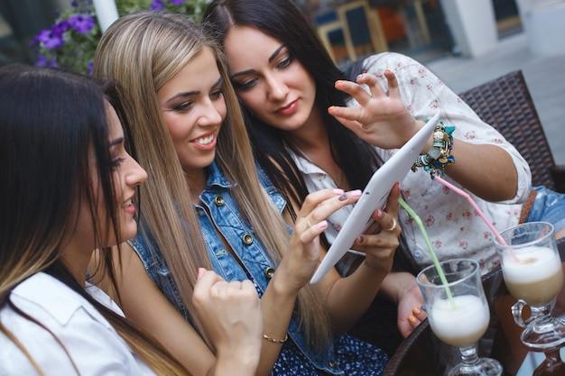 オンラインショッピングを行う陽気なガールフレンド。カフェテリアで若い笑う女性。楽しんで笑顔の若い女の子