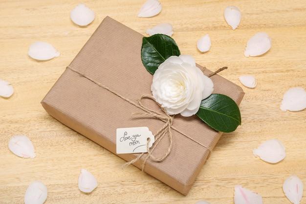 Концепция день матери. подарочная коробка с этикеткой и цветком. ручной текст люблю тебя мама