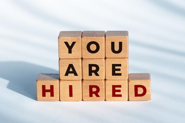 あなたは木製のサイコロに雇われたフレーズです。雇用またはビジネスコンセプト