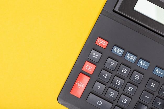 黄色の背景上の電卓。経済やビジネスの概念の背景。コピースペース