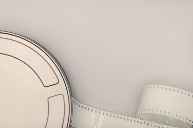 映画フィルム缶とテーブルの上のフィルムストリップ。映画やテレビの背景。トップビュー、コピースペース