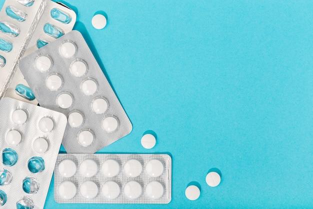 Таблетки на синем фоне. концепция медицины, здравоохранения и фармации. копировать пространство