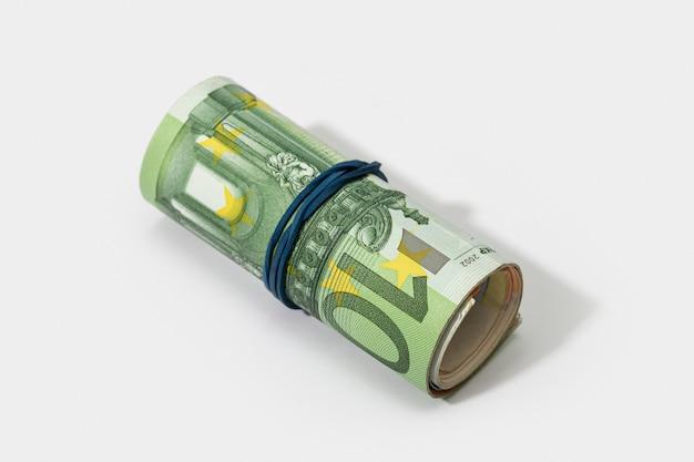 白い背景で隔離のゴムバンドでユーロ紙幣のロール。お金の概念