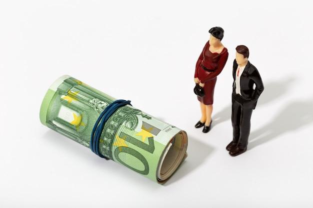 お金のロールを見ているカップルの人間の表現。金融、投資または節約のコンセプト
