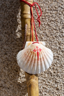 花崗岩の石の壁に寄りかかったカミノデサンティアゴの杖と貝殻。サンティアゴデコンポステーラ巡礼のコンセプト