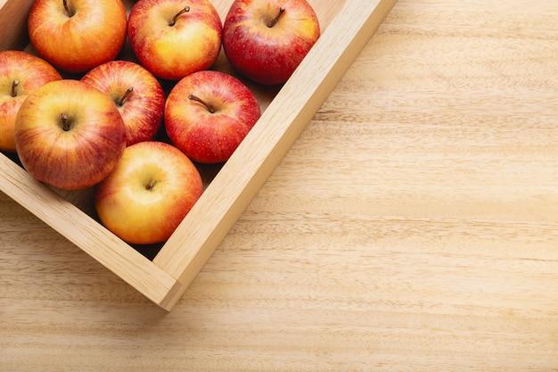 コピースペースと新鮮なリンゴの背景。木製のテーブルの木枠に赤いリンゴ