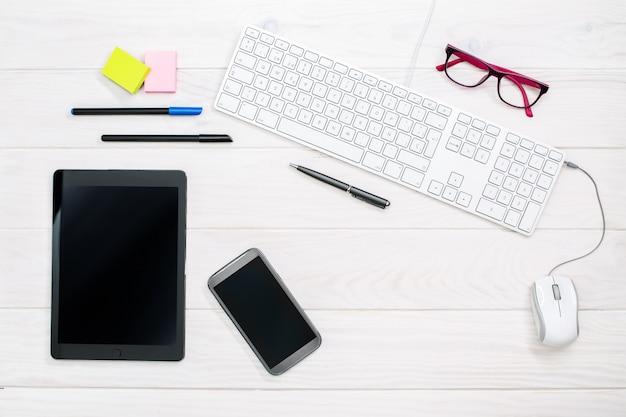 白のキーボード、スマートフォン、タブレット、オフィス用品とワークスペース
