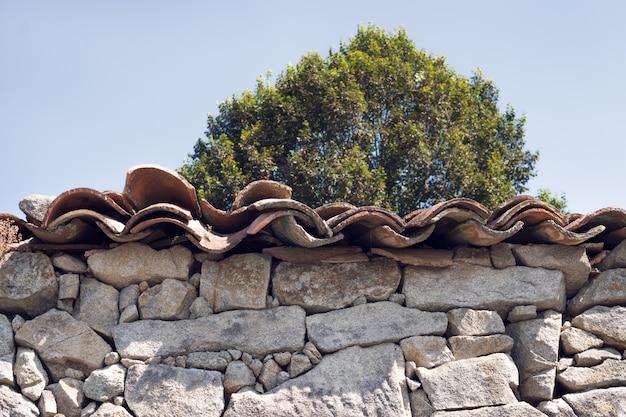 アンティークドライ石積みの石の壁と屋根の粘土タイルの詳細