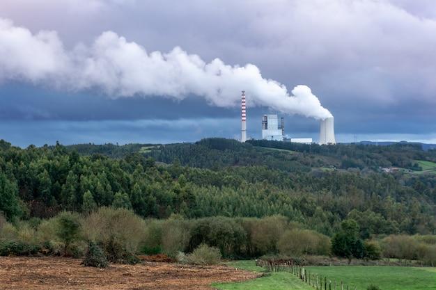 Угольная электростанция загрязняет воздух. толстая дымящаяся дымовая труба к небу. концепция проблемы загрязнения окружающей среды