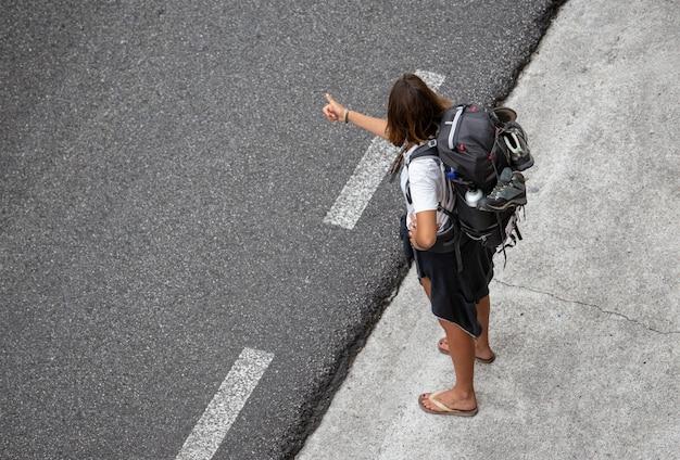 Молодая женщина путешествует автостопом возле дороги