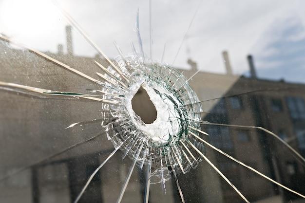 破壊行為または暴力の概念。割れたガラスの穴