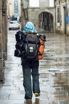 サンティアゴデコンポステーラの旧市街の雨の日の通りを歩いて巡礼者