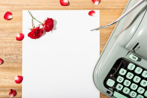 ラブレター。空白の紙、レトロタイプライター、赤いバラと花びらの机