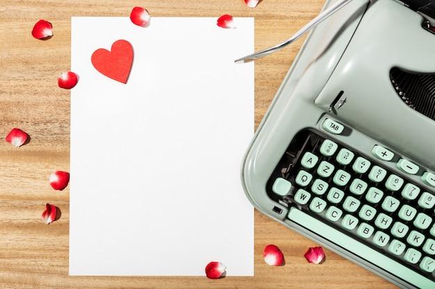 ラブレター。白紙の紙、レトロタイプライター、赤いハートのデスク
