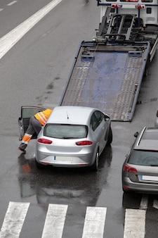 フラットベッドレッカー車のプラットフォームにロードする準備ができている都市通りの道路で壊れた車のシーン