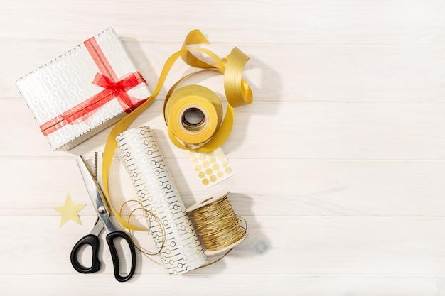 Плоская планировка рождественских подарков, декоративной бумаги, лент и ножниц.