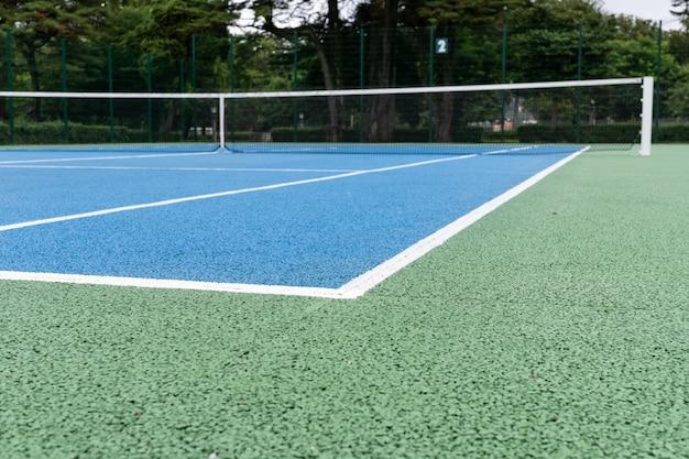 青いテニスコート。屋外の晴れた日。テニスのコンセプト。コピースペース