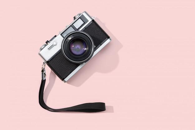ピンクの背景に分離されたフラットレイアウトフィルムカメラ。コピースペース