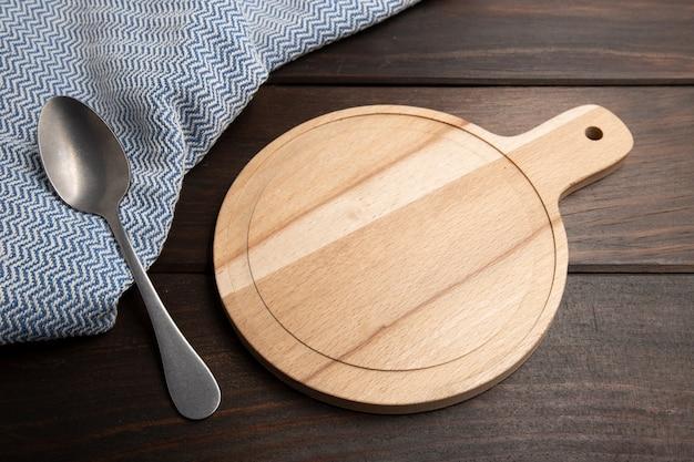 スプーンで木製のテーブルに空のまな板。
