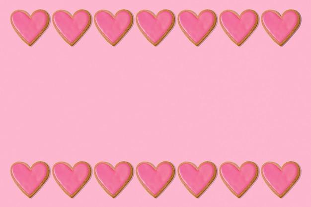 バレンタイングリーティングカードの背景。ピンクのハートクッキーフレームの境界線。コピースペース