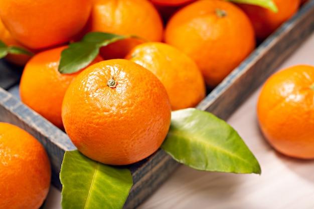 木製のテーブルの上の葉で新鮮なオレンジ色の果物