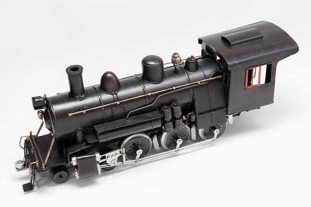 白で隔離される古い鉄道機械ブリキのおもちゃ