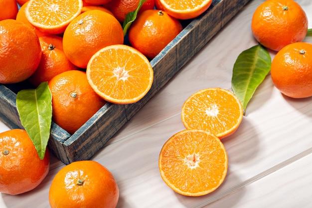 Свежие фрукты мандарин с листьями на деревянный стол