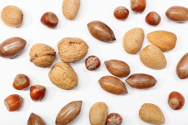 白で隔離されるさまざまなナッツ